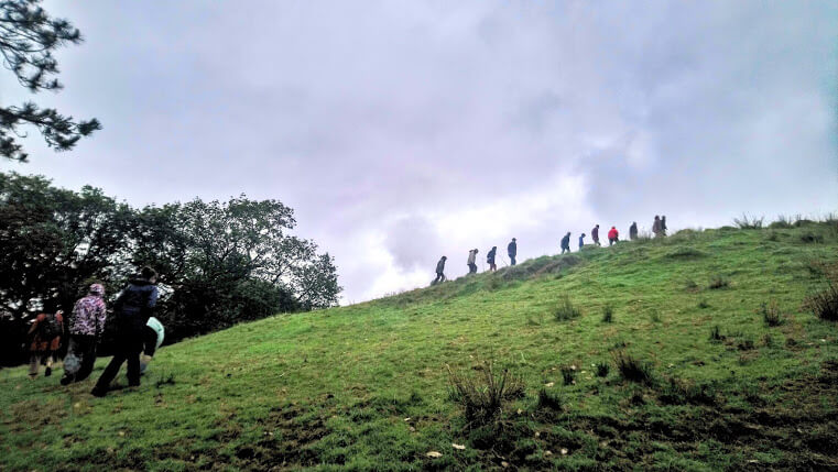 People walking up a hill during trip to Wales